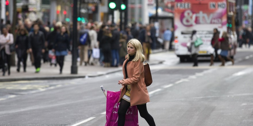 A shopper crosses Oxford Street, one of the main shopping streets in central London, on December 20, 2015, on the final shopping Sunday before Christmas. AFP PHOTO / JUSTIN TALLISJUSTIN TALLIS/AFP/Getty Images